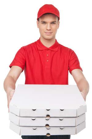 caja de pizza: Aqu� est� su pizza! Repartidor joven alegre que estira hacia fuera una pila de cajas de pizza mientras aislados en blanco