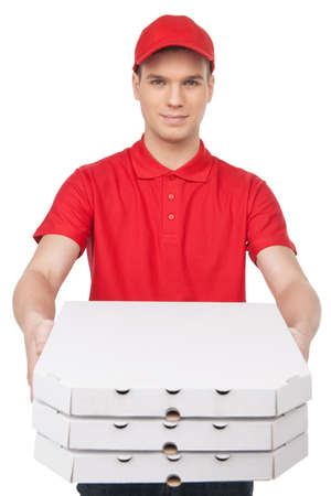 pizza delivery: Here is your pizza! Cheerful young deliveryman stretching out a stack of pizza boxes while isolated on white