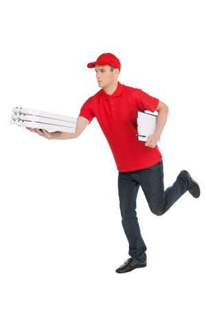 Hurrying to be in time. Cheerful young deliveryman running with a stack of pizza in his hand while isolated on white photo