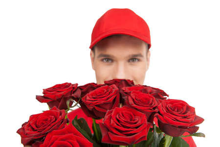 deliveryman: Beautiful roses for you! Close-up of deliveryman holding a bunch of red roses