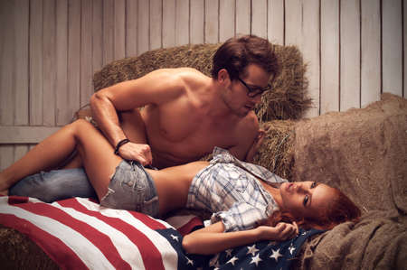 Sexy couple pose sur le drapeau am�ricain. Homme regardant fille avec passion photo