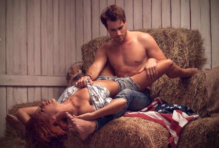 sexuales: Sexy pareja teniendo sexo en el pajar. Hombre atractivo con el torso desnudo Foto de archivo