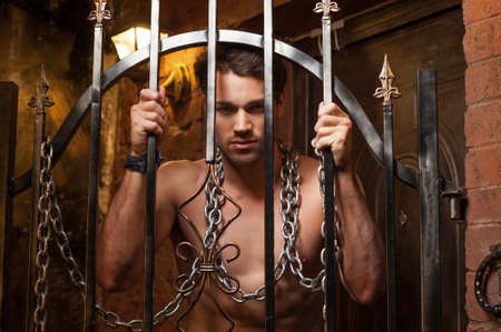 Sexy man standing behind metal gates. With metal chain on neck photo