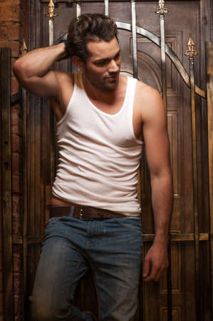 prisoner man: Sexy man in white T-shirt and jeans. Standing with gates on background