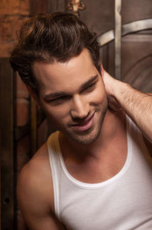 Portrait of sexy man in white T-shirt. Smiling and looking away photo