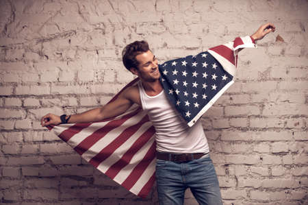 Handsome man posing with American flag. Smile and using flag like cloak photo