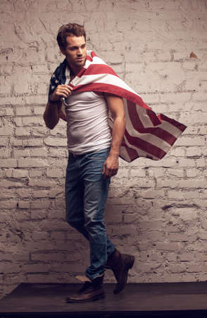 Handsome man walking using American flag like a cloak. Looking away photo