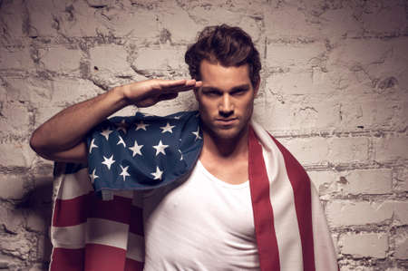 sexy army: Young handsome man posing with American flag. Saluting like soldier
