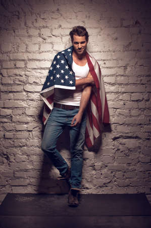 Sexy man resting on the wall. Having American flag on his shoulders photo