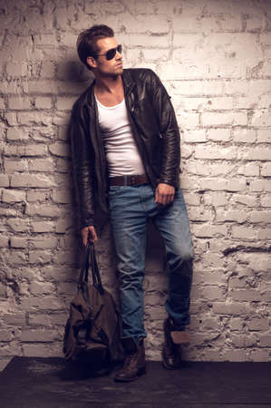 Sexy man with handbag. Standing in black leather jacket and jeans Zdjęcie Seryjne