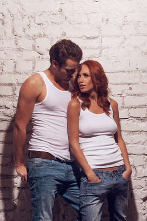 Beautiful sexy couple looking at each other. Wearing white T-shirts and jeans photo