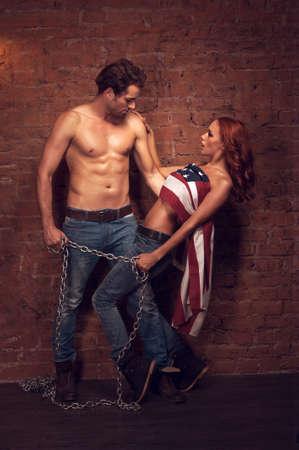 sexy nackte frau: Gut aussehend sexy Mann mit einem M�dchen mit einer Kette. Sch�ne M�dchen deckt ihren K�rper mit der amerikanischen Flagge