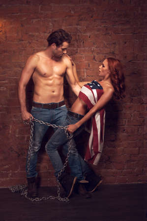Handsome sexy man holding a girl with a chain. Beautiful girl covers her body with American flag photo