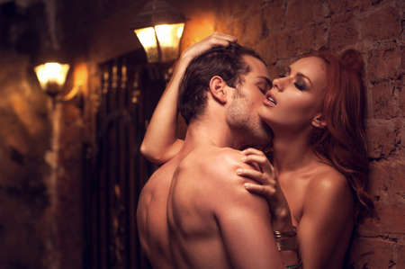 Beautiful couple having sex in gorgeous place. Man kissing woman's neck Stock Photo
