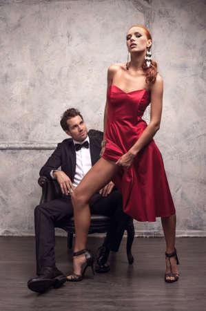 mujeres elegantes: Hermosa ni�a de vestido rojo tratando de seducir al hombre guapo. Mostrando su esbelta pierna