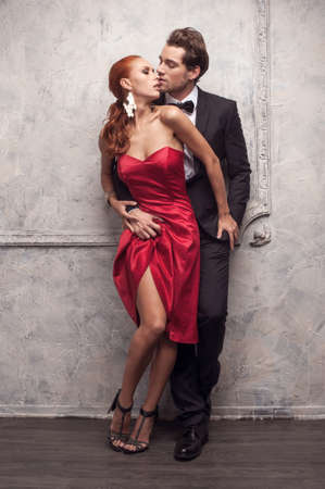 seducing: Beautiful couple in classical outfits. Standing and kissing with passion Stock Photo