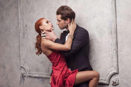 classic: Hermoso hombre va a besar a su hermosa mujer. De pie en el vestido rojo cl�sico