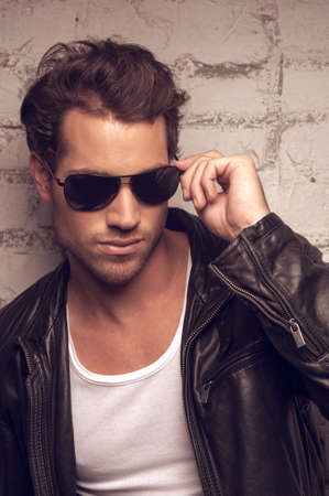 Portrait of sexy man in sun glasses. Holding on side of the glasses Stock Photo
