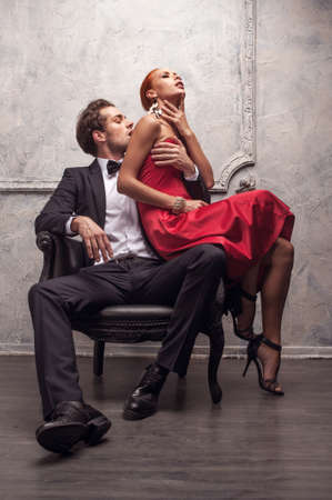 Elegant handsome man kissing his girlfriend in a shoulder. Girl sitting on his knees