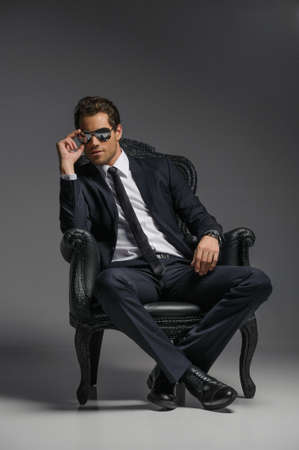 male model: I am a boss. Confident young businessmen in sunglasses sitting on the vintage chair while isolated on grey