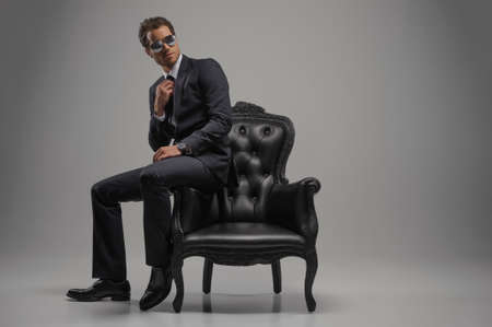 black suit: Looking just perfect. Full length of confident young businessmen in sunglasses sitting on the vintage chair while isolated on grey