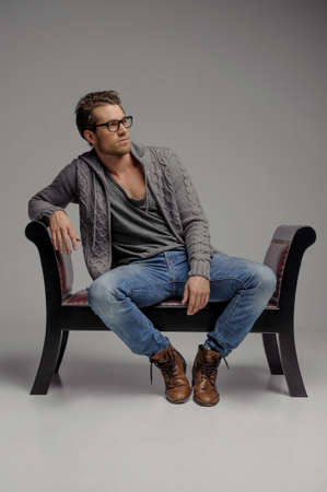 Thinking of the future. Handsome young men in glasses sitting on the chair and looking away while isolated on grey photo
