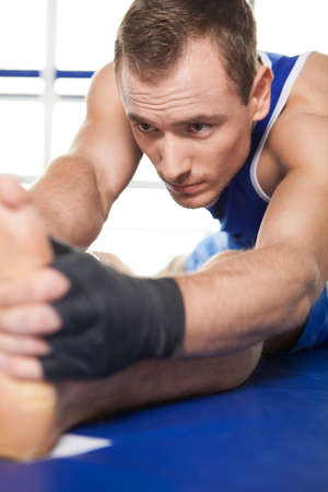 sports wear: Boxer warming up. Young sportsman in gloves warming up and stretching Stock Photo