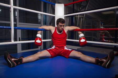 defeated: Defeated boxer. Frustrated young boxer sitting on the boxing ring