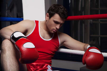 defeated: Defeated boxer. Disappointed young boxer sitting on the boxing ring and looking down Stock Photo