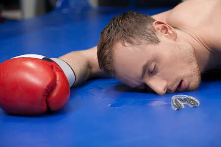 defeated: Defeated boxer. Close-up of defeated boxer lying down on the boxing ring with closed eyes Stock Photo