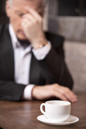 Depressed businessman. Depressed mature businessman sitting at the restaurant with his head in hand and the cup of coffee at the foreground photo