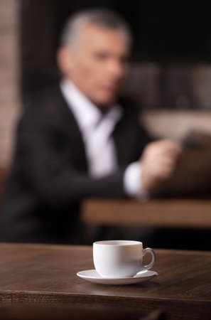 Break time. Mature businessman reading a newspaper with a cup of coffee on the foreground photo