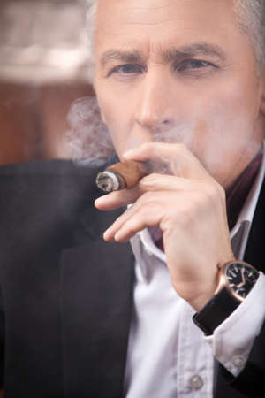 Smoking a cigar. Successful mature businessman smoking a cigar and looking at camera photo