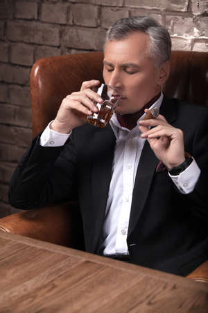 Special moments. Confident mature businessman drinking whiskey and smoking a cigar photo