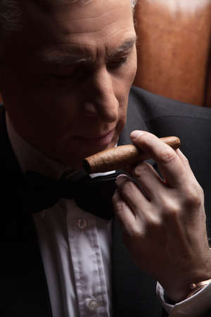 Man smelling a cigar. Close-up of confident mature businessman smelling a cigar photo