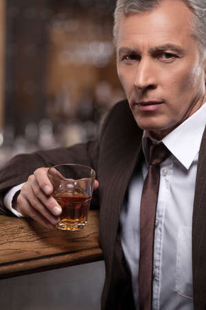 Relaxing after a hard working day. Confident mature businessman sitting at the bar and drinking whiskey photo