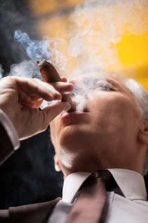 cigarro: Fumar un buen puro. Ángulo de visión baja de la alta cigarro fumar hombre de negocios Foto de archivo