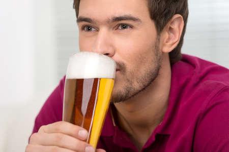 hombre tomando cerveza: Los hombres bebiendo cerveza. Retrato de los hombres jóvenes y apuestos bebiendo cerveza y mirando a otro lado Foto de archivo