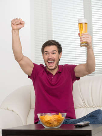 Goal! Happy young men holding a beer glass in his hand and expressing positivity photo