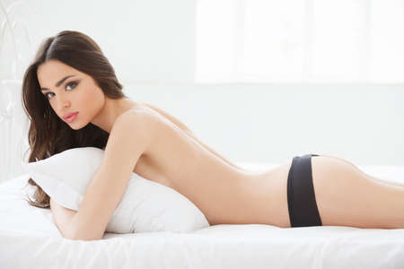 Beautiful young women in lingerie lying on her front and looking at camera Stock Photo