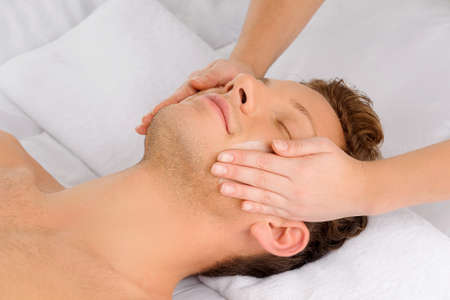 Facial massage. Top view of relaxed young men lying on the massage table while massage therapist massaging his face photo