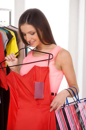 Woman shopping. Beautiful young woman holding red dress in retail store photo