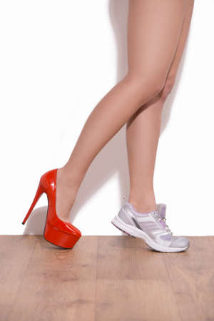 Making a choice. Close-up of woman wearing heeled shoe and sneakers on different legs photo