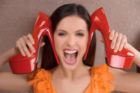 Her favourite shoes. Excited young woman holding red heeled shoes near face and shouting photo