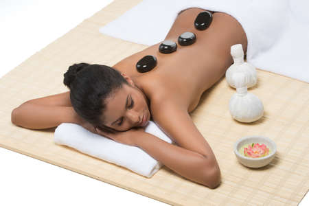 Relaxed women at SPA. Top view of beautiful young women lying on front with SPA stones on her back photo