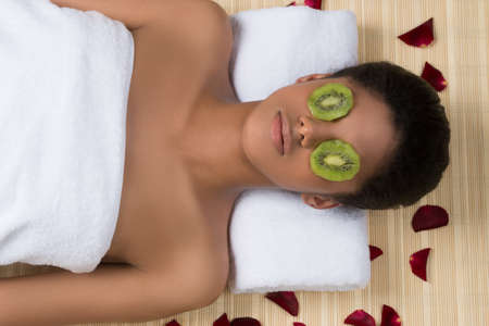 Beauty treatment. Top view of beautiful young women lying with pieces of kiwi on her face photo