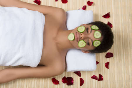 Beauty treatment. Top view of beautiful young women lying with pieces of cucumber on her face photo