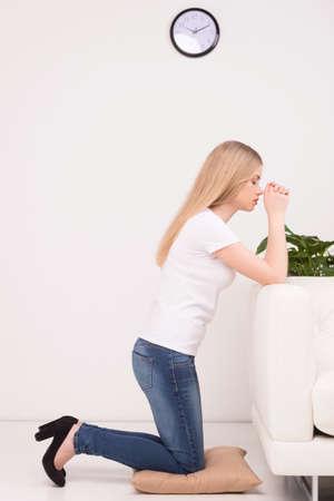 kneeling woman: Girl praying. Side view of beautiful young blond hair woman praying at home