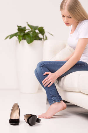 Tired woman. Side view of tired young woman sitting on the couch and touching leg