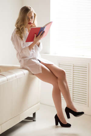 legs crossed at knee: Woman reading book. Thoughtful young blond hair woman leaning oat the couch and reading book Stock Photo